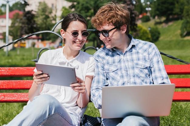 Junges glückliches paar, das im park arbeitet