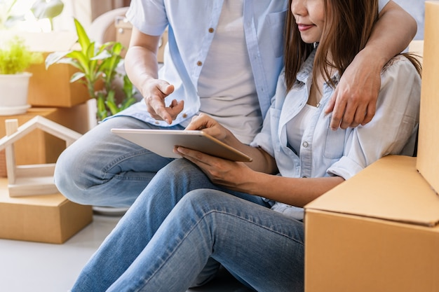 Junges glückliches paar, das in ein neues haus einzieht, auf dem boden sitzt und sich entspannt und nach wohnideen auf dem tablet sucht