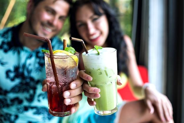 Junges glückliches paar, das leckere süße cocktails an der tropischen bar trinkt, lächelt und spaß hat, helle kleidung und positive gefühle.