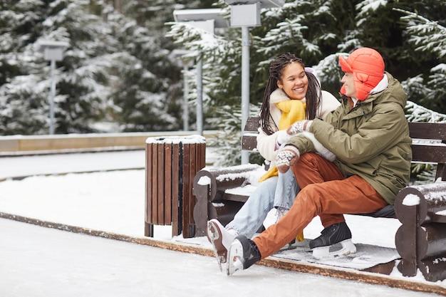 Junges glückliches paar, das miteinander spricht, während auf bank im freien im winterpark sitzt