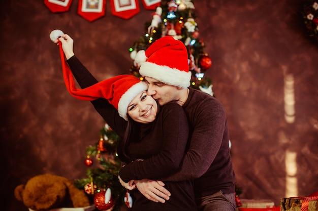 Junges glückliches paar, das nahe dem weihnachtsbaum umarmt