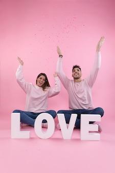 Junges glückliches paar, das nahe großem liebeszeichen zwischen fliegenden konfetti sitzt