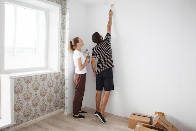 Junges glückliches paar, das reparaturen in einer neuen wohnung tut. malen mit einer walze einer weißen wand in einem neuen gebäude.