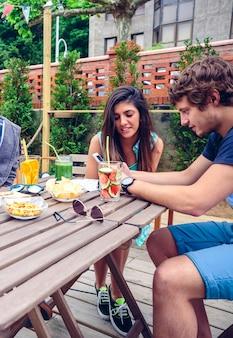 Junges glückliches paar, das smartphone an einem sommertag im freien am tisch mit gesunden getränken sieht