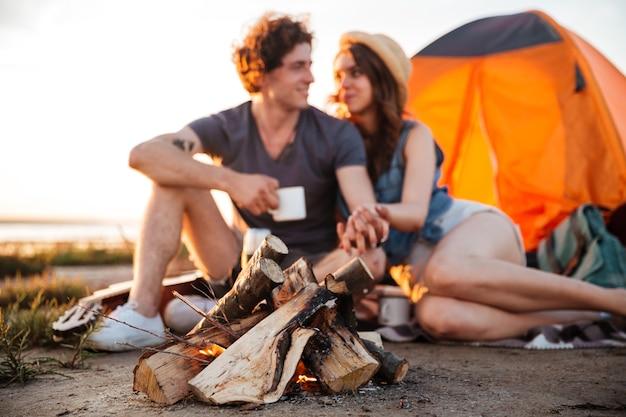 Junges glückliches paar, das tee am lagerfeuer trinkt und sich beim zelten ansieht