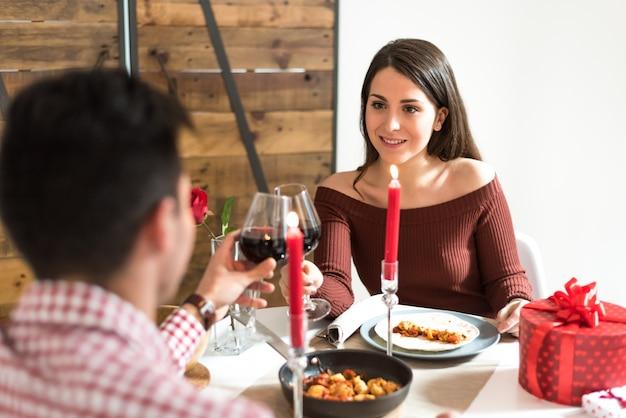 Junges glückliches paar, das valentinstag mit einem abendessen zu hause trinkt wein, beifall feiert.