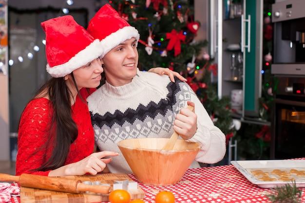 Junges glückliches paar, das weihnachtskuchen backt