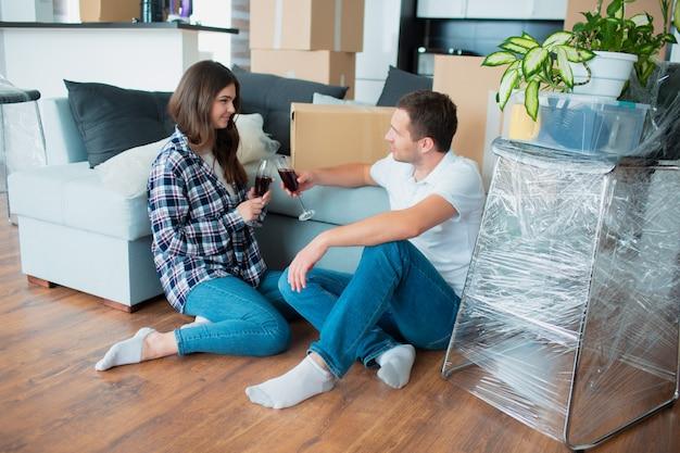 Junges glückliches paar, das wein trinkt, den umzug in ein neues zuhause feiert und zwischen kisten sitzt.