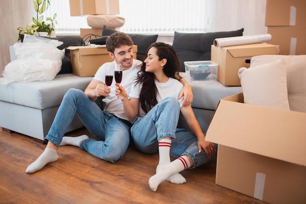 Junges glückliches paar, das wein trinkt, den umzug in ein neues zuhause feiert und zwischen kisten sitzt