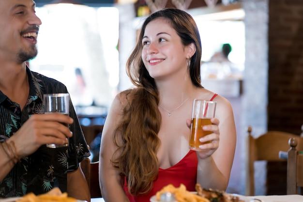 Junges glückliches paar, das zeit zusammen genießt, während es ein datum in einem restaurant hat.