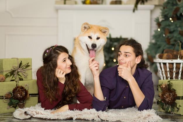 Junges glückliches paar, das zu hause entzückenden hund akitas inu mit auf dem boden für weihnachtsfeiertage streichelt.