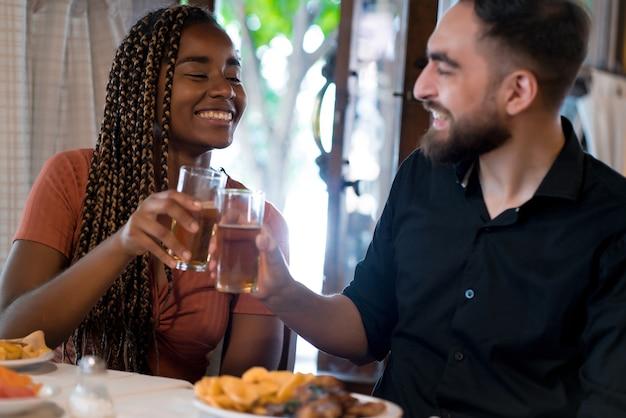 Junges glückliches paar, das zusammen eine mahlzeit genießt, während es sich in einem restaurant verabredet.