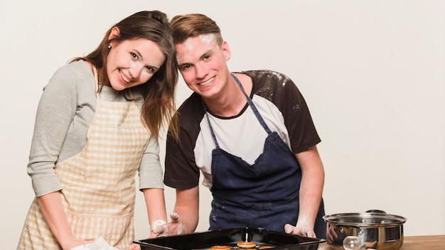 Junges glückliches paar, das zusammen kocht