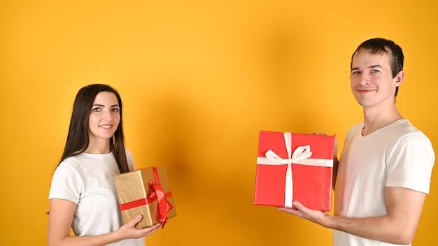 Junges glückliches paar erhielt geschenke voneinander auf gelb