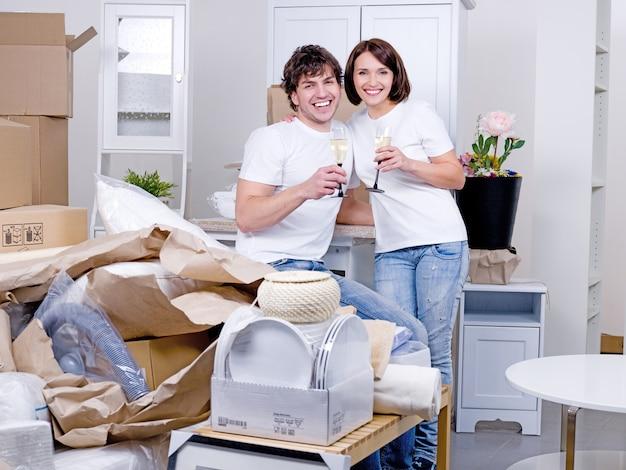 Junges glückliches paar feiert neues zuhause zusammen mit einem glas champagner - drinnen