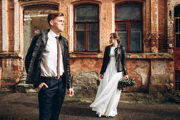Junges glückliches paar geht auf einer stadtstraße nach regen. braut und bräutigam mit lederjacken im freien. herbsthochzeit.