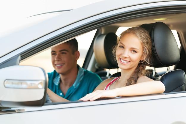 Junges glückliches paar im auto lächelnd - konzept des autokaufs