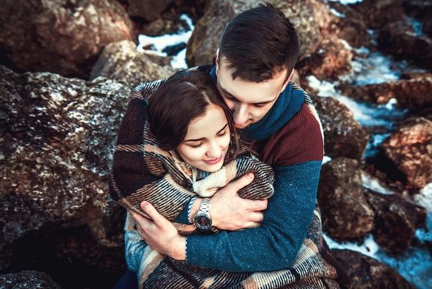 Junges glückliches paar im freien auf den steinen