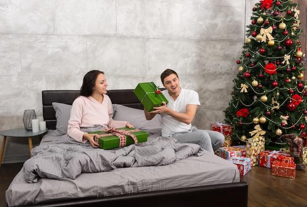 Junges glückliches paar im pyjama freut sich über seine geschenke, während es am weihnachtsmorgen im schlafzimmer im loft-stil auf dem bett sitzt