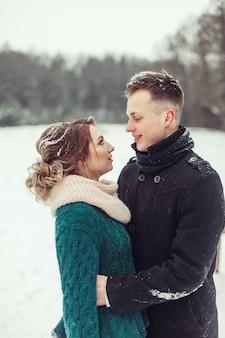 Junges glückliches paar im schneebedeckten wald des winters, der sich umarmt.