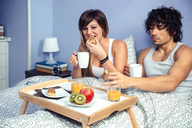 Junges glückliches paar in der liebe beim frühstück im bett serviert über einem tablett zu hause. paar zu hause lifestyle-konzept.