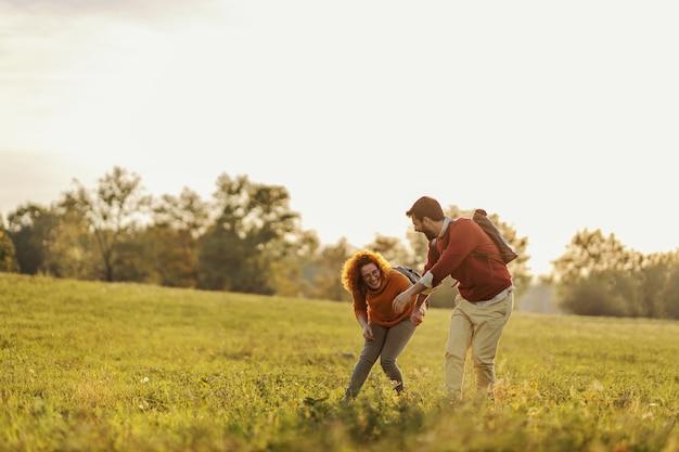 Junges glückliches paar in der liebe, die hände hält und auf wiese läuft. es ist ein wunderschöner sonniger herbsttag.