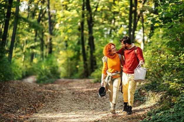 Junges glückliches paar in der liebe, die in der natur umarmt und geht. paar hält picknickausrüstung.
