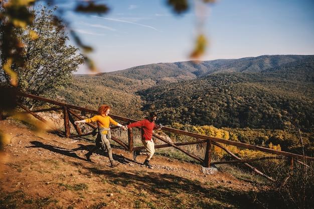 Junges glückliches paar in der liebe, die wochenende in der natur an einem sonnigen herbsttag verbringt. paar händchen haltend und rennend.