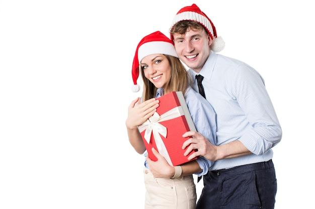 Junges glückliches paar in der weihnachtsmannmütze mit geschenkboxen