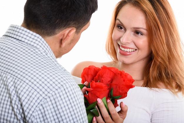 Junges glückliches paar lächelnd und verliebt in glückliche frau, die rote rosen hält