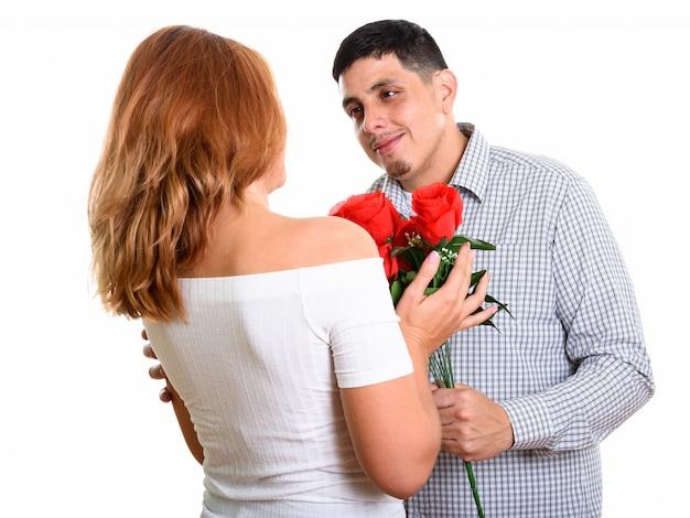 Junges glückliches paar lächelnd und verliebt in mann, der freundin rote rosen gibt