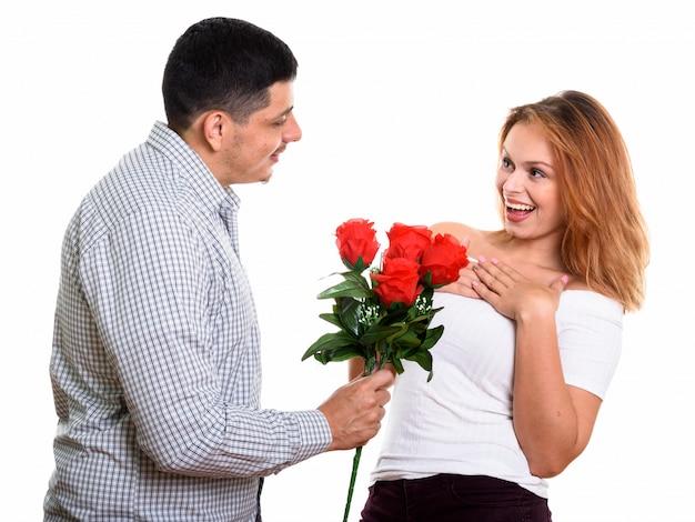 Junges glückliches paar lächelnd und verliebt in mann, der rote rosen und frau gibt, die überrascht schauen