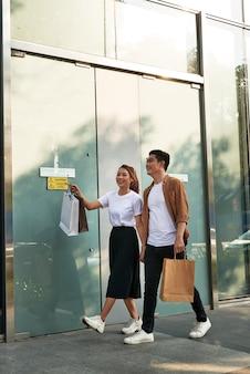 Junges glückliches paar mit einkaufstüten in der stadt.