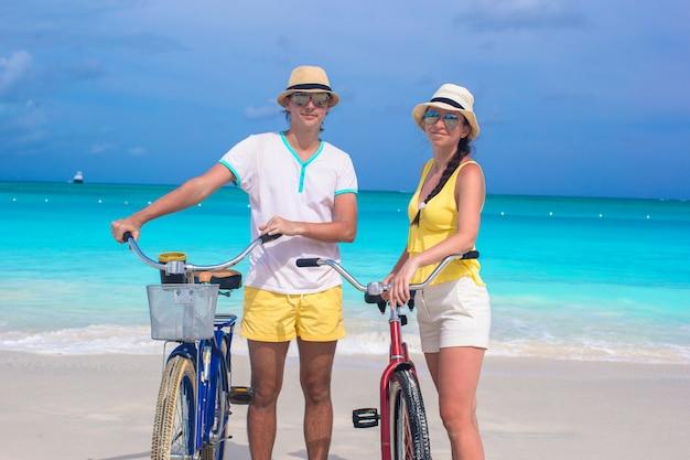 Junges glückliches paar mit fahrrädern auf weißem sandigem strand