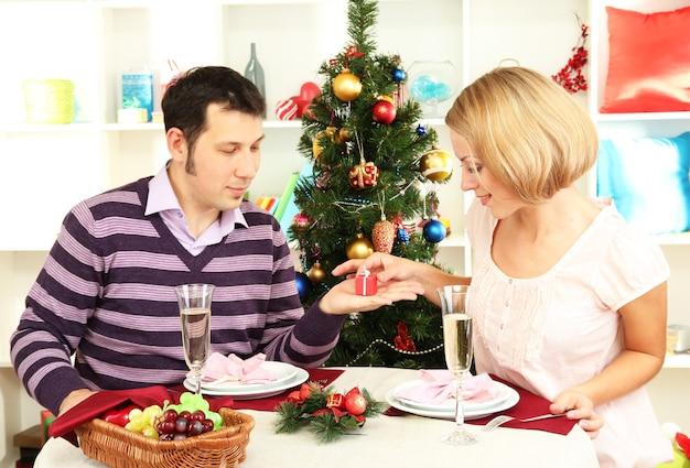 Junges glückliches paar mit geschenken, die am tisch nahe weihnachtsbaum sitzen