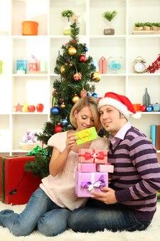 Junges glückliches paar mit geschenken, die zu hause in der nähe des weihnachtsbaums sitzen