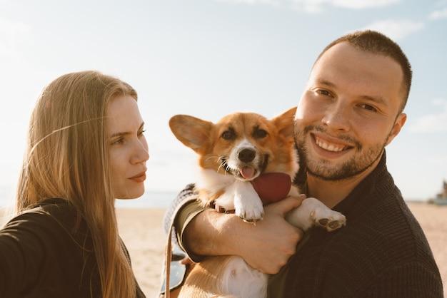 Junges glückliches paar mit hund, der selfie am strand nimmt. schöne frau und mann und corgi