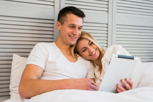 Junges glückliches paar mit tablette unter decke auf bett