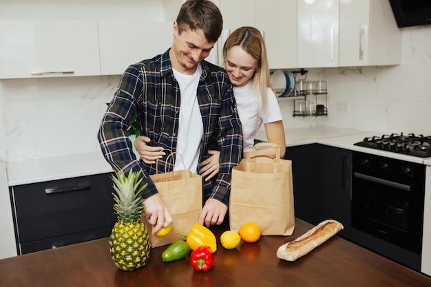 Junges glückliches paar nach dem besuch des supermarktes.