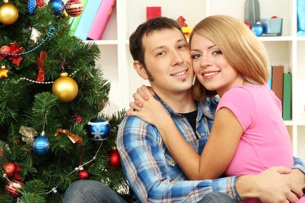 Junges glückliches paar nahe einem weihnachtsbaum zu hause