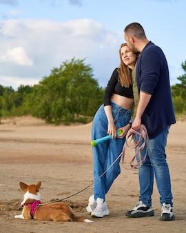 Junges glückliches paar und hund, die am strand gegen kiefern und sand stehen, mann, der frau sanft küsst