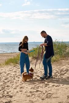 Junges glückliches paar und hund, die entlang strand gehen. frau, die mit haustier durch spielzeug spielt.