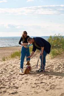Junges glückliches paar und hund, die entlang strand gehen