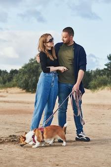 Junges glückliches paar und hund stehen am strand gegen kiefern und sand. schöner mann und schöne frau