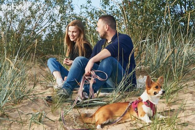 Junges glückliches paar von mann und frau mit corgi-hund, der am sand sitzt