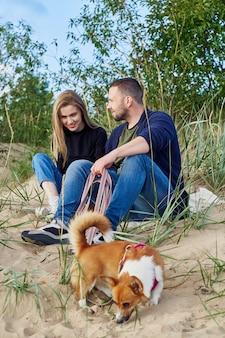 Junges glückliches paar von mann und frau mit corgi-hund