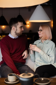 Junges glückliches romantisches liebespaar, das tee im café trinkt.