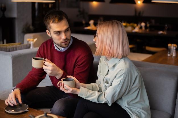 Junges glückliches romantisches liebespaar, das tee trinkt