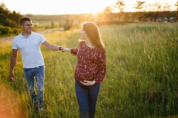 Junges glückliches schönes paar in der liebe, die zusammen auf gras- und baumparklandschaft geht