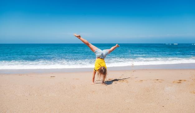 Junges glückliches sportliches mädchen in einem gelben t-shirt, das auf händen auf dem sand, dem seehorizont und den weißen wellen an einem sonnigen tag steht, freudige bewegung der urlaubsfreiheit
